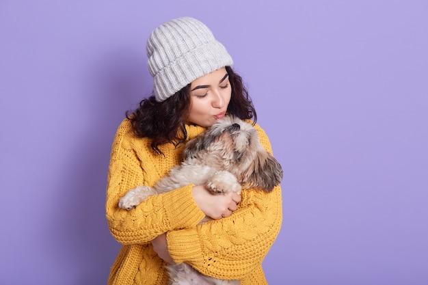 Mulher jovem e bonita com cachorro pequinês engraçado no espaço lilás Foto gratuita