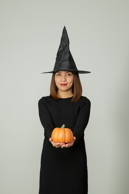 Mulher jovem e bonita com chapéu de bruxa segurando uma lanterna de abóbora de halloween Foto Premium