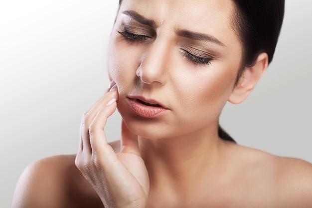 Mulher jovem e bonita com dor de dente, cárie, problemas dentários, sensações dolorosas no rosto, maquiagem linda. Foto Premium