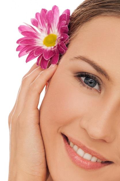 Mulher jovem e bonita com flores no cabelo Foto gratuita