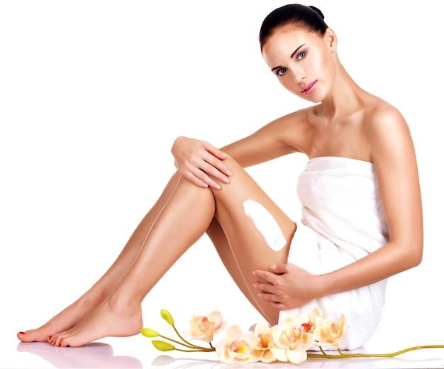 Mulher jovem e bonita com flores usando o creme isolado no branco Foto gratuita
