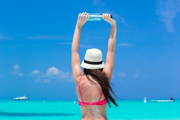 Mulher jovem e bonita com garrafa na praia Foto Premium