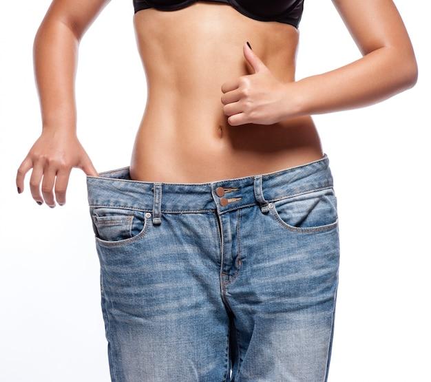 Mulher jovem e bonita com jeans grandes, isolado no branco Foto Premium