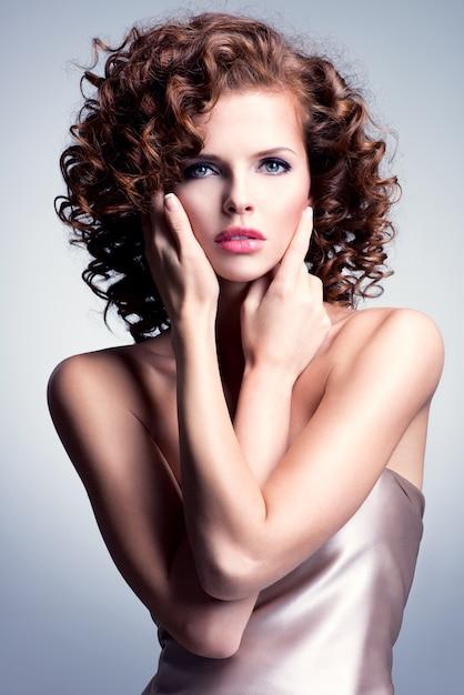 Mulher jovem e bonita com maquiagem glamour e penteado elegante, tocando seu rosto. modelo posando no estúdio sobre fundo cinza. Foto gratuita