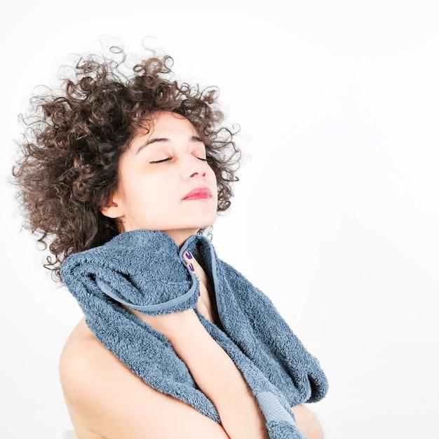 Mulher jovem e bonita com o olho fechado enxuga o rosto com a toalha contra o pano de fundo branco Foto gratuita