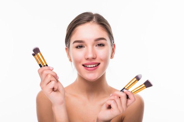 Mulher jovem e bonita com pincéis de maquiagem perto do rosto, isolado na parede branca Foto gratuita