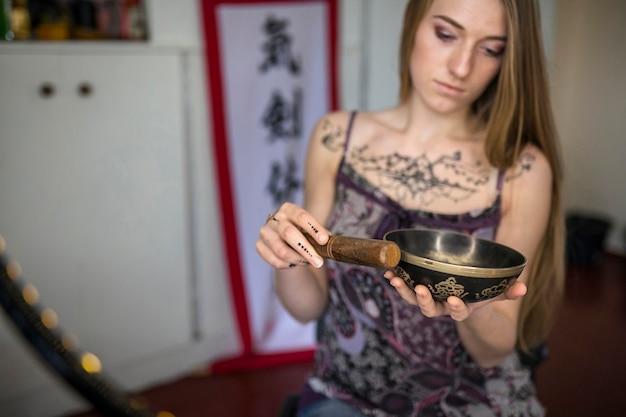 Mulher jovem e bonita com tatuagem de heena jogando tibetano cantando tigela na natureza Foto gratuita