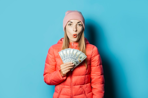 Mulher jovem e bonita com um chapéu e uma jaqueta de inverno com uma cara surpresa segurando dinheiro Foto Premium