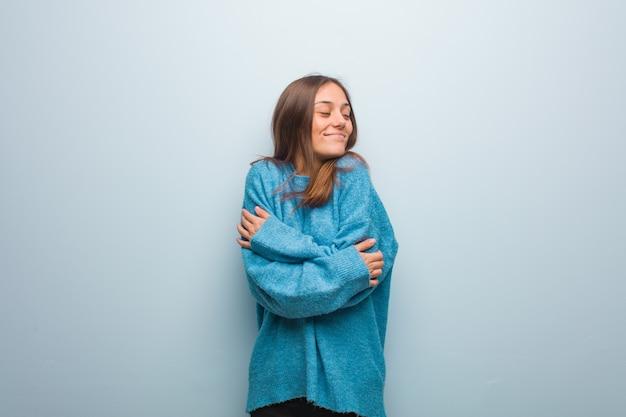 Mulher jovem e bonita com um suéter azul dando um abraço Foto Premium