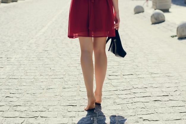 Mulher jovem e bonita com vestido vermelho, andando pela cidade sem sapatos, ela está segurando o salto alto na mão. foto de close-up das pernas compridas com os pés descalços de uma mulher contra a estrada, vista de trás Foto Premium