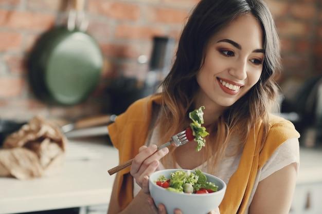 Mulher jovem e bonita comendo uma salada saudável Foto gratuita