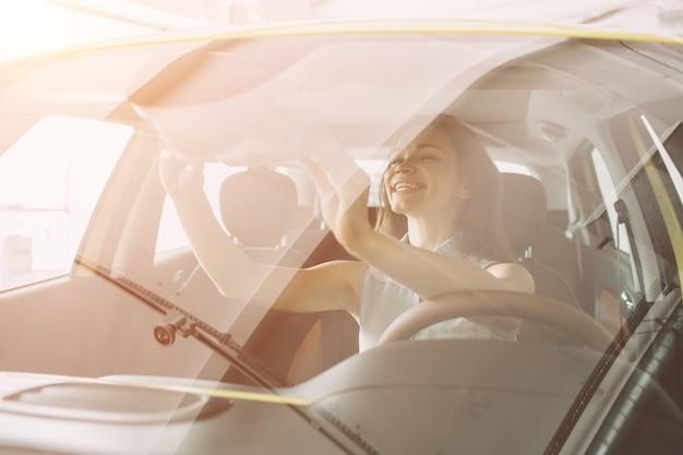 Mulher jovem e bonita comprando um carro na concessionária. modelo feminino sentado dentro do veículo no showroom. Foto Premium