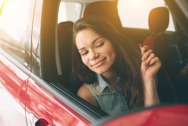 Mulher jovem e bonita comprando um carro na concessionária Foto Premium