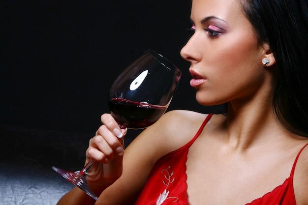 Mulher jovem e bonita drinkink vinho Foto gratuita