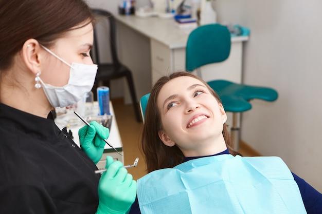 Mulher jovem e bonita e positiva sorrindo amplamente após um check-up dentário regular, olhando para sua higienista feminina, mostrando seus dentes brancos perfeitos Foto gratuita