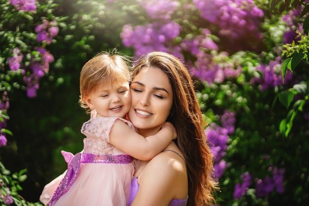 Mulher jovem e bonita e sua filha encantadora estão abraçando e sorrindo. dia das mães Foto Premium