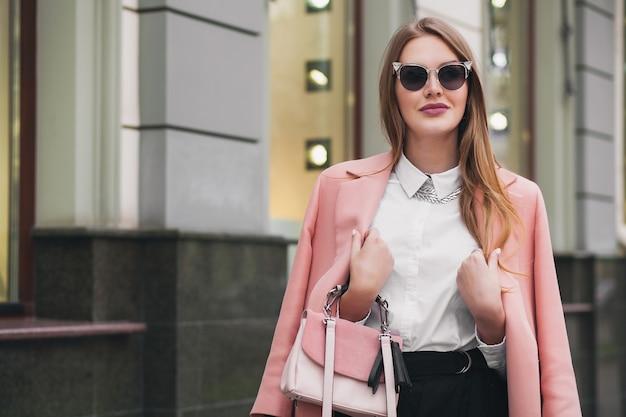 Mulher jovem e bonita elegante andando na rua, vestindo um casaco rosa, bolsa, óculos de sol, camisa branca, saia preta, roupa da moda, tendência do outono, sorrindo feliz, acessórios Foto gratuita