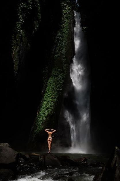 Mulher jovem e bonita em biquíni relaxante em frente a cachoeira. ecoturismo conceito imagem viagens menina Foto Premium