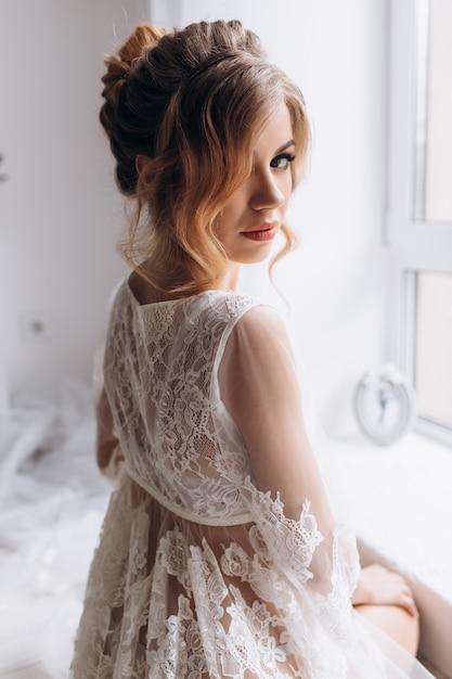 Mulher jovem e bonita em lingerie branca posa em roupão de seda branco no quarto de hotel brilhante Foto gratuita