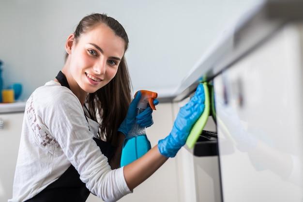 Mulher jovem e bonita em luvas de proteção, limpeza de forno com pano Foto gratuita