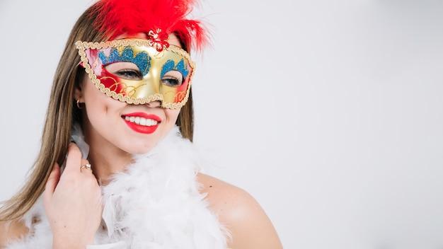 Mulher jovem e bonita em máscara de carnaval e boa de penas no fundo branco Foto gratuita