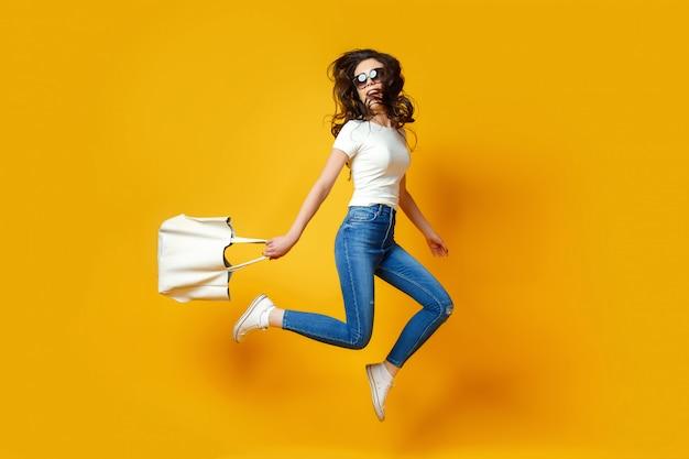 Mulher jovem e bonita em óculos de sol, camisa branca, calça jeans azul pulando com saco sobre o fundo amarelo Foto Premium