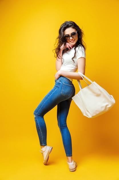 Mulher jovem e bonita em óculos de sol, camisa branca, jeans azul posando com saco Foto Premium