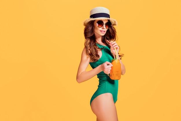 Mulher jovem e bonita em trajes de banho esmeralda e chapéu de palha segurando o jarro com bebida gelada Foto Premium
