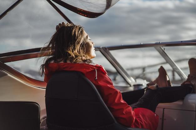 Mulher jovem e bonita em uma capa de chuva vermelha monta um iate privado. estocolmo, suécia Foto gratuita