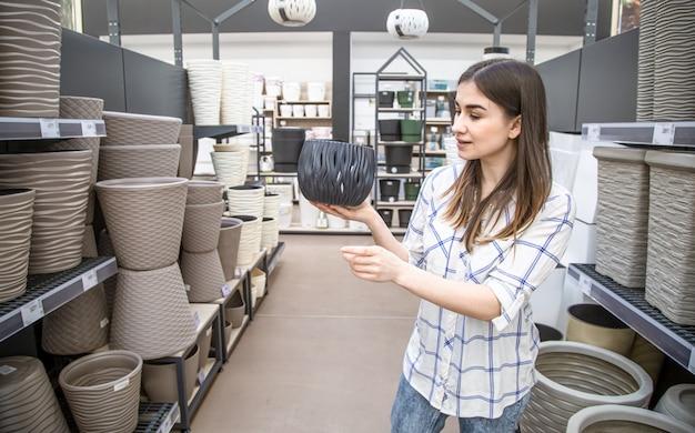 Mulher jovem e bonita em uma loja de flores escolhe um vaso de flores. Foto gratuita