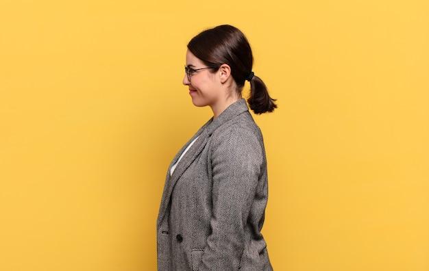 Mulher jovem e bonita em vista de perfil, olhando para copiar o espaço à frente, pensando, imaginando ou sonhando acordada Foto Premium