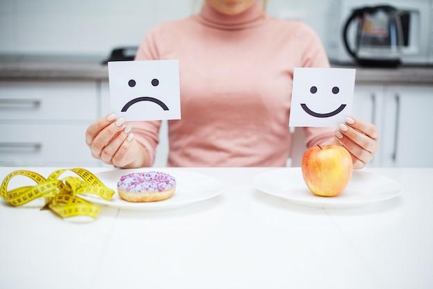 Mulher jovem e bonita escolhendo entre comida saudável e junk food Foto Premium