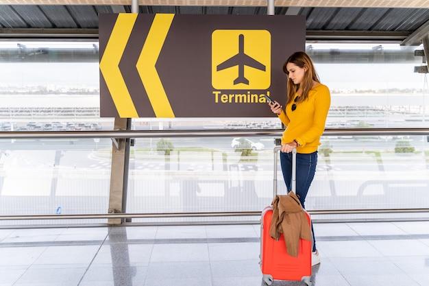 Mulher jovem e bonita esperando com seu telefone celular e bagagem no aeroporto Foto Premium