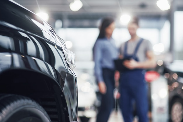 Mulher jovem e bonita está falando com o mecânico de carro bonito enquanto repara um carro na concessionária Foto gratuita