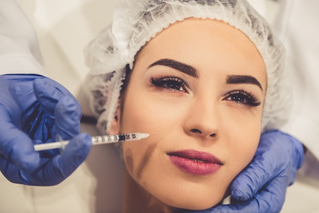 Mulher jovem e bonita está recebendo uma injeção no rosto. Foto Premium