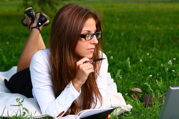 Mulher jovem e bonita estudando no parque Foto gratuita