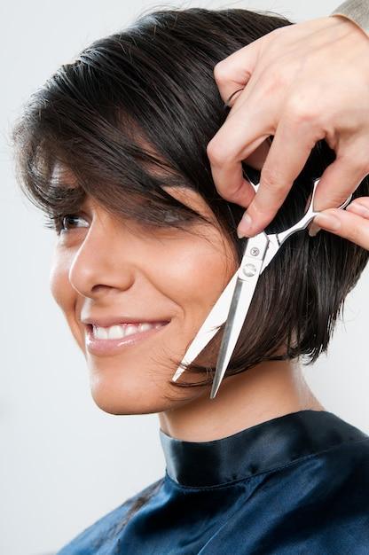 Mulher jovem e bonita feliz cortando cabelo no salão de cabeleireiro Foto Premium