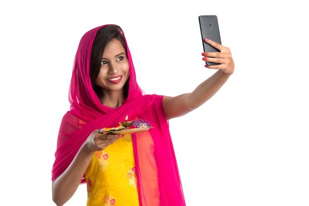 Mulher jovem e bonita feliz tomando selfie com pooja thali usando um telefone celular ou smartphone em branco Foto Premium