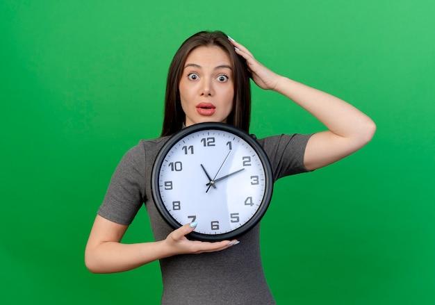 Mulher jovem e bonita impressionada segurando o relógio e colocando a mão na cabeça isolada sobre fundo verde Foto gratuita