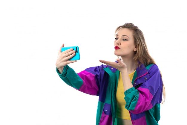Mulher jovem e bonita jaqueta colorida usando smartphone para foto de selfie Foto gratuita