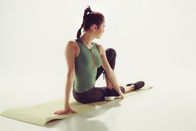 Mulher jovem e bonita magro fazendo exercícios de alongamento na academia contra estúdio branco Foto gratuita