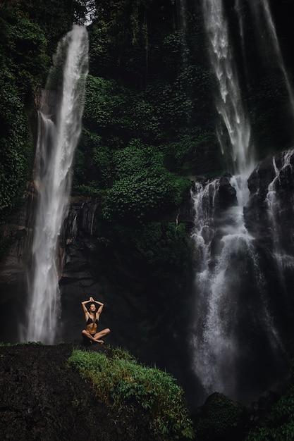 Mulher jovem e bonita meditando na posição de lótus enquanto fazia ioga em uma floresta maravilhosa perto de cachoeira. linda fêmea praticando yoga na rocha perto de cachoeira tropical Foto Premium