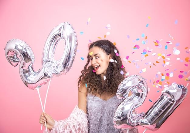 Mulher jovem e bonita morena com cabelos cacheados segurando balões de prata para o conceito de ano novo. Foto Premium