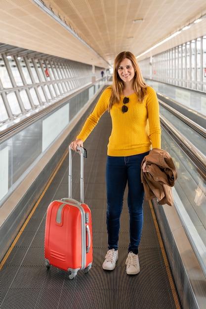 Mulher jovem e bonita muito feliz andando na esteira no aeroporto com sua bagagem Foto Premium