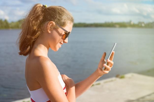 Mulher jovem e bonita no parque usando o celular Foto Premium