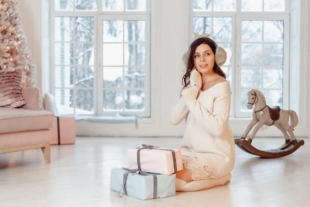 Mulher jovem e bonita no vestido branco, posando com caixas de presente Foto gratuita