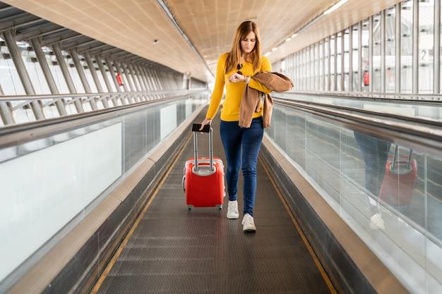 Mulher jovem e bonita olhando para o relógio no aeroporto ou estação com sua bagagem Foto Premium