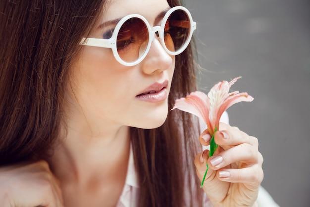 Mulher jovem e bonita posando em um dia ensolarado de verão com uma pequena flor bonita Foto gratuita