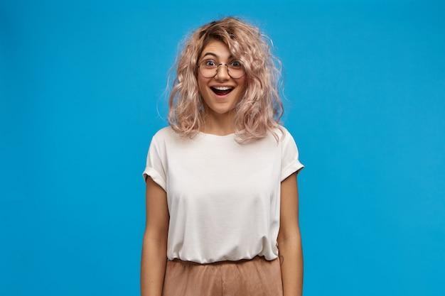Mulher jovem e bonita radiante, vestindo uma camiseta branca enorme e óculos redondos, feliz por receber notícias positivas inesperadas, abrindo a boca amplamente Foto gratuita