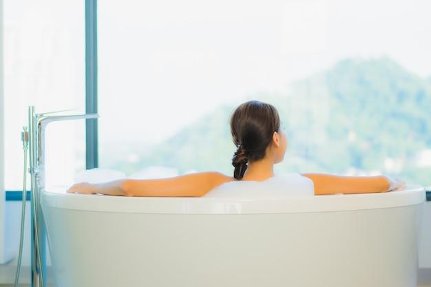 Mulher jovem e bonita relaxando na banheira Foto gratuita
